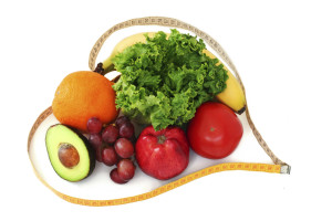Fresh fruits and vegetables surrounded by a heart shaped measuring tape on white background